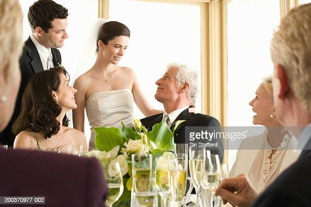Bride and groom visiting  wedding guests at table