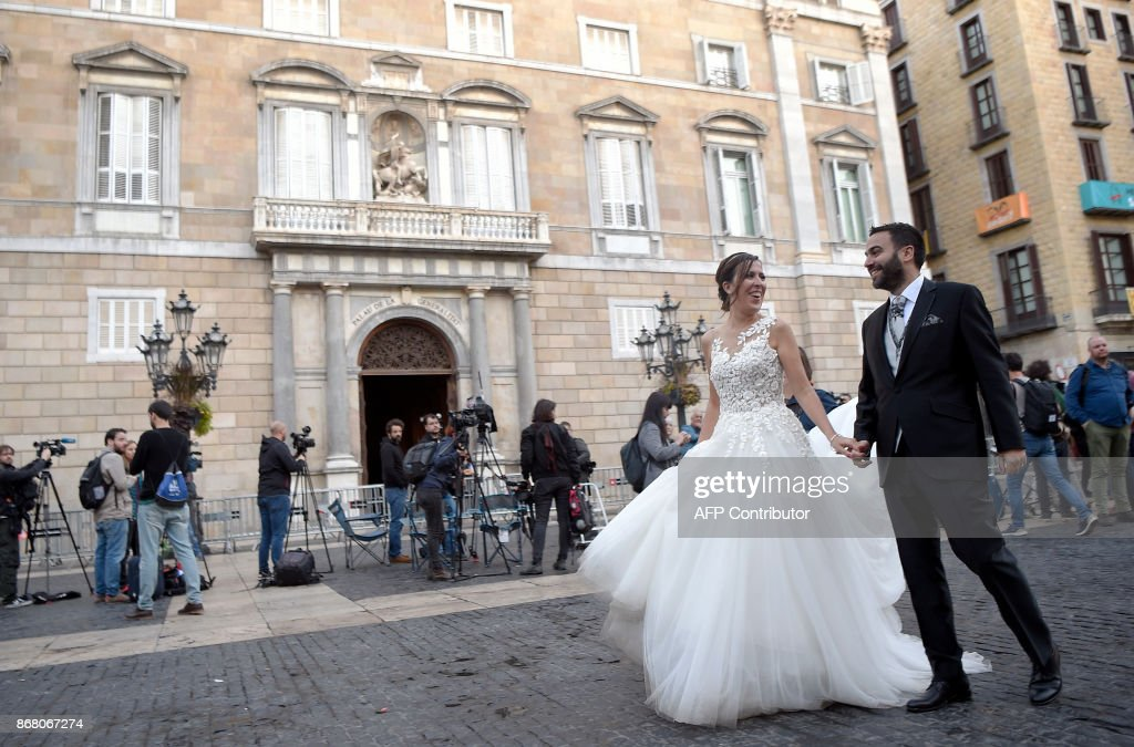 A bride and groom walk in front of the 'Generalitat' palace (Catalan government headquarters) in Barcelona on October 30, 2017. Spain enters uncharted and potentially perilous territory today as Madrid moves to take over the running of Catalonia in response to the rebellious region's parliament unilaterally declaring independence. GENE