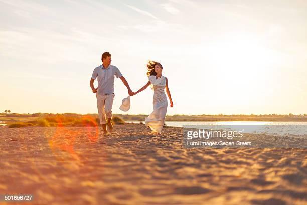 Bride and groom walking across beach at sunset, Dalmatia, Croatia