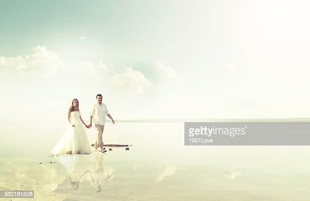 Bride and groom walking at beach