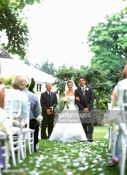 bride and groom walking down aisle after wedding ceremony, smiling - religious occupation stock pictures, royalty-free photos & images
