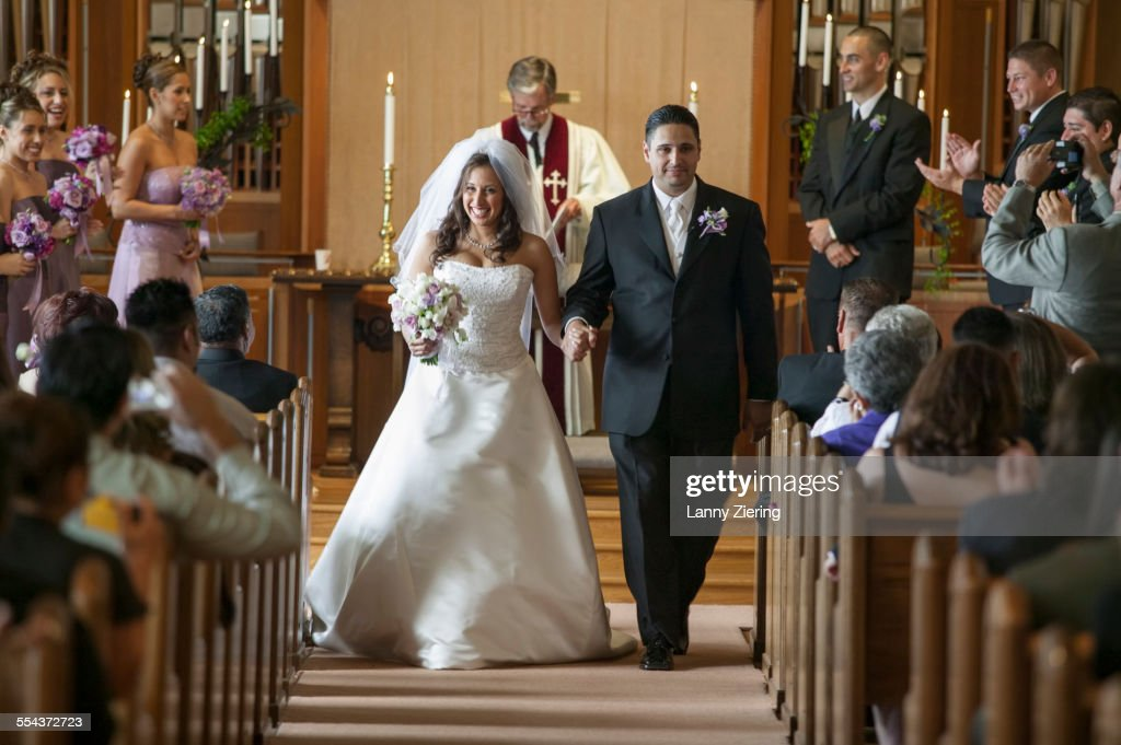 Bride and groom walking down aisle during wedding ceremony : Stock Photo