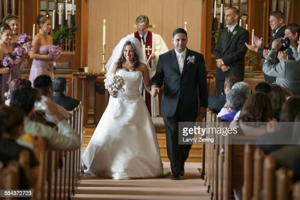 Bride and groom walking down aisle during wedding ceremony