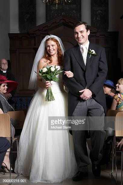 bride and groom walking down aisle, smiling - tail coat stock pictures, royalty-free photos & images