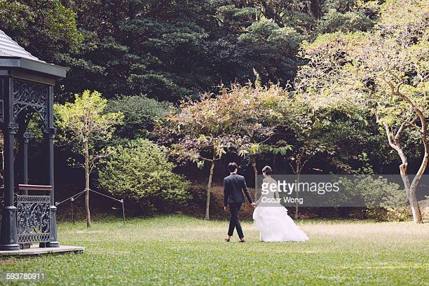 Bride and groom walking in park hand in hand