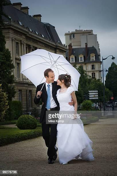 Bride and groom walking in the rain