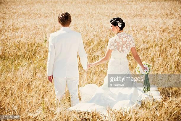 Braut und Bräutigam zu Fuß auf einem Feld