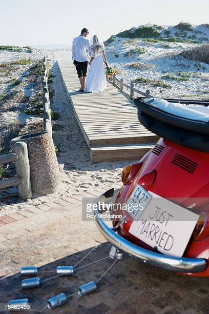 Bride and groom walking on beach, car in foreground