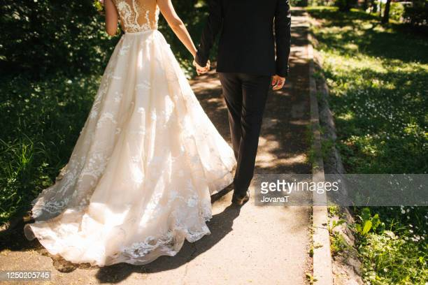 bride and groom walking on pavements - bride stock pictures, royalty-free photos & images