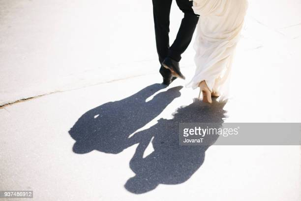 bride and groom walking on sunny day - dress shoe stock pictures, royalty-free photos & images
