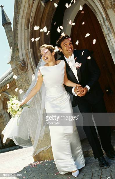bride and groom walking outside a church - church wedding decorations stock pictures, royalty-free photos & images