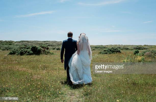 bride and groom walking through a field of green on their wedding day - ceremony stock pictures, royalty-free photos & images