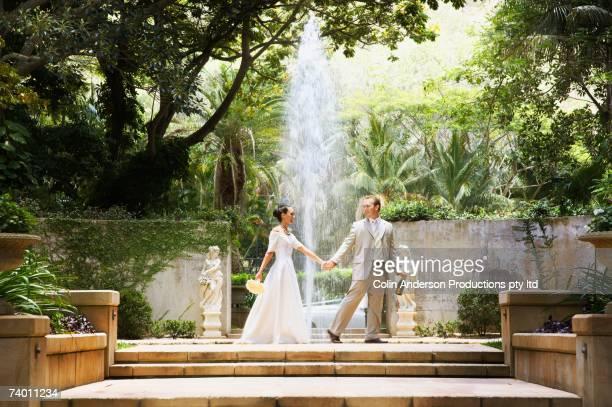 bride and groom walking through jungle ruins - tropical tree stockfoto's en -beelden