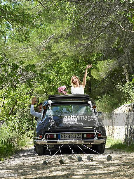 Bride and groom waving from wedding car