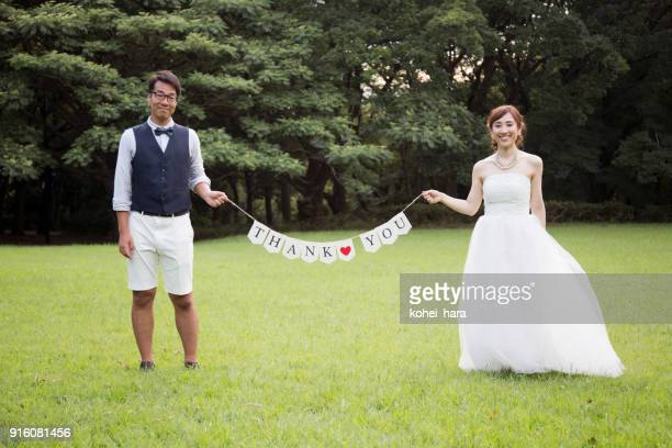 Bride and groom wearing wedding costumes holding flags with message which say 'THANK YOU' in the park
