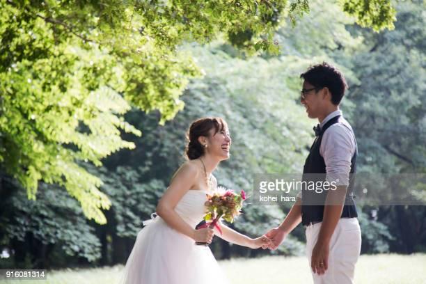 結婚式の衣装を着て新郎新婦が公園でリラックス - 結婚式 ストックフォトと画像