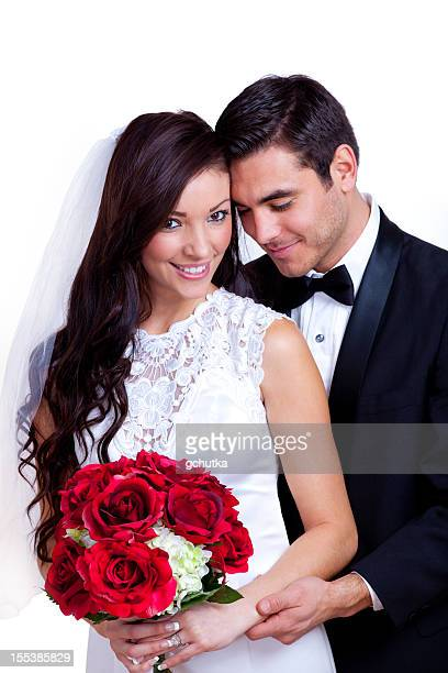 A bride and groom with a red bouquet of flowers