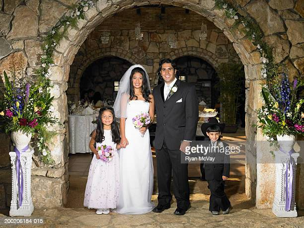 Bride and groom with ring bearer (3-5) and flower girl (6-8), portrait