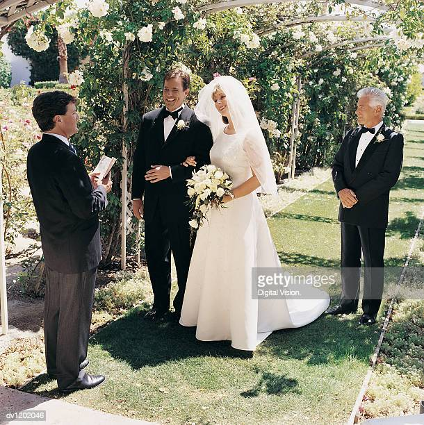 Bride and Groom With the Father at a Marriage Ceremony in a Garden