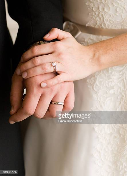 Bride and groom with wedding rings, holding hands, mid section