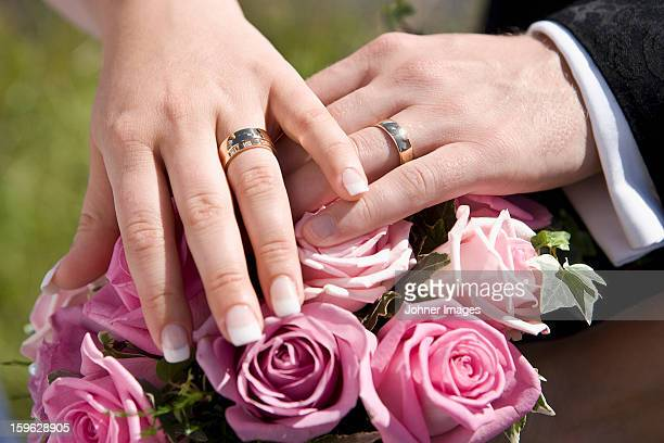Bride and groom with wedding rings on top of bouquet