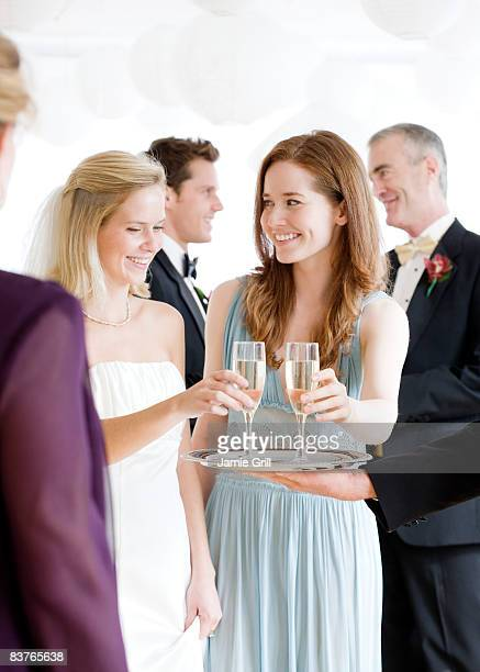 bride and guest taking a drink from the waiter - wedding guest stock pictures, royalty-free photos & images