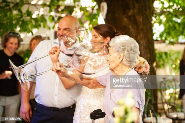 bride and her mother in law drinking wine from large wineglass at wedding celebration - mother in law stock pictures, royalty-free photos & images