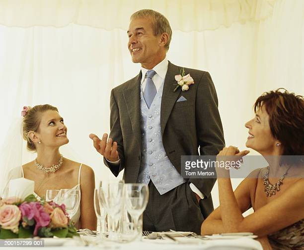 Bride and parents at head table, father making speach