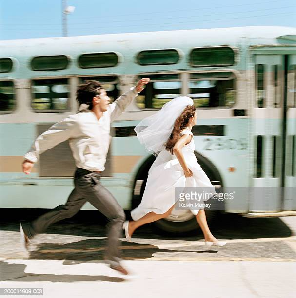 Bride and young man running to catch bus (blurred motion)