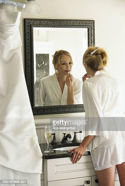 Bride applying makeup in bathroom mirror, rear view