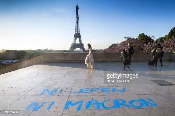 A bride arrives to pose for a photographer in front of the Eiffel Tower at the Trocadero plazza where a graffiti on the ground refering to the second...