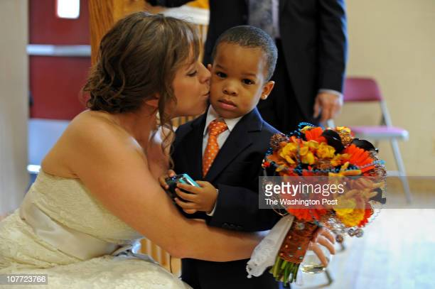 Bride Ashley Adams kisses Christopher Reed ring bearer just before the wedding ceremony on November 6 2010