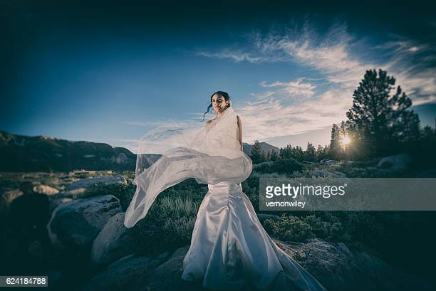 Bride at sunset in the mountains on windy day