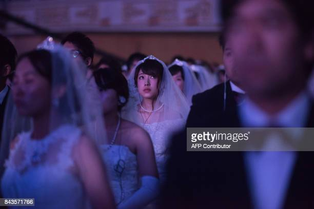 TOPSHOT A bride attends a mass wedding ceremony held by the unification church entitled a 'cosmic blessing ceremony' in Gapyeong on September 7 2017...