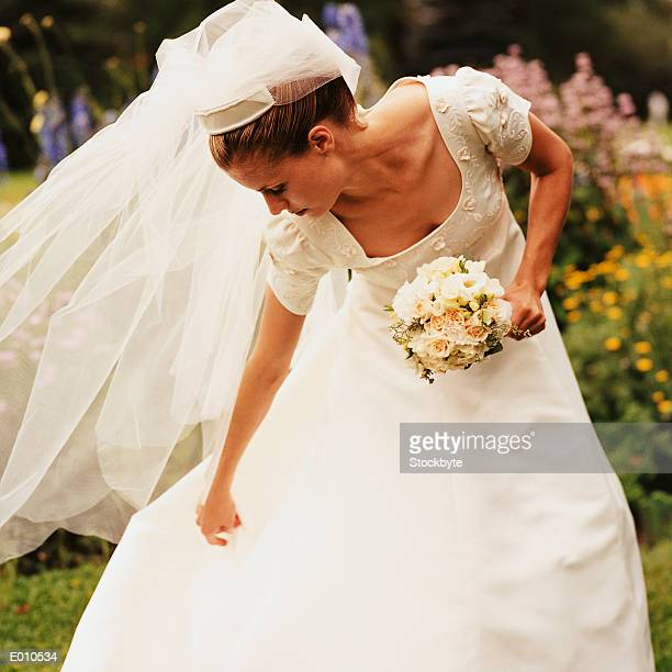 bride bending over to adjust gown - bend over cleavage stock photos and pictures