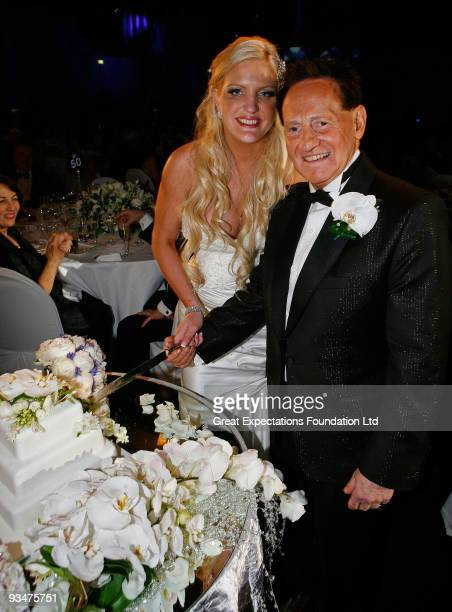 Bride Brynne Gordon and groom Geoffrey Edelsten pose for a photograph as they cut the wedding cake during the wedding of Geoffrey Edelsten and Brynne...