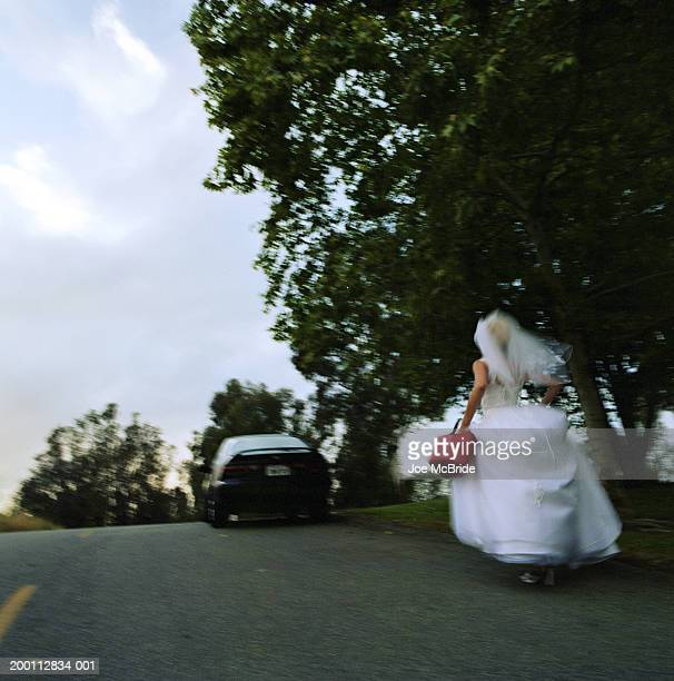 Bride carrying gas can, running toward stalled car, rear view
