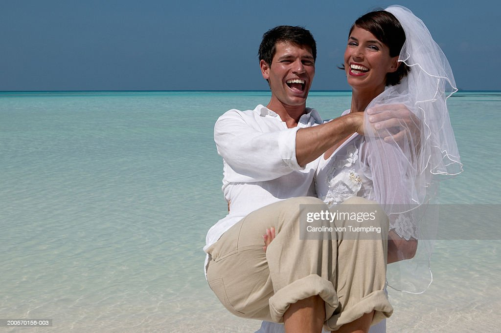 Bride carrying groom walking on beach, laughing, portrait : Stock Photo