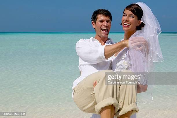 Bride carrying groom walking on beach, laughing, portrait