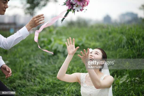 Bride catching bouquet from groom