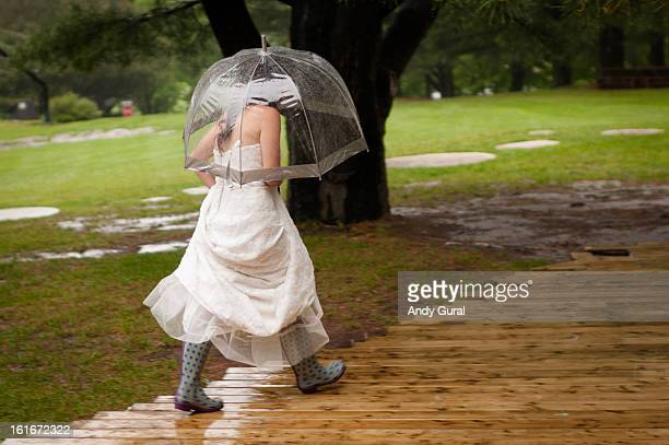 CONTENT] A bride caught in the rain dashes between buildings wearing spotted Wellington Boots The bride in her wedding dress is holding an umbrella