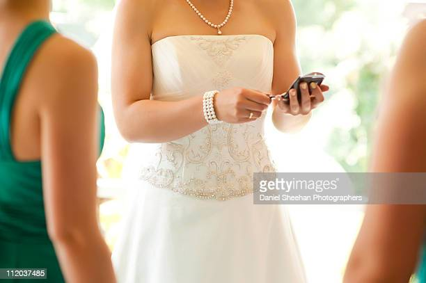 bride checking mobile phone - bridesmaid stock pictures, royalty-free photos & images