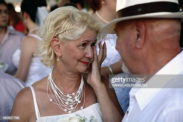 A bride cries at the end of a mass civil wedding ceremony for foreign couples organised by the Larnaca municipality and travel agents in the southern...