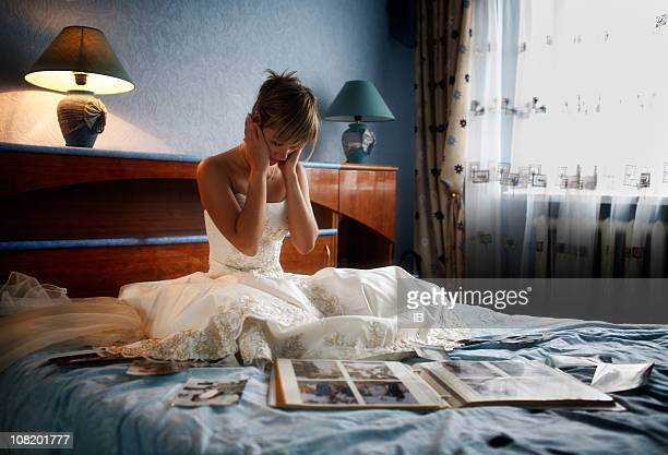 Bride Cries on Bed Surrounded by Photo Albums