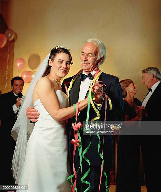 Bride dancing with mature male guest at wedding reception, portrait