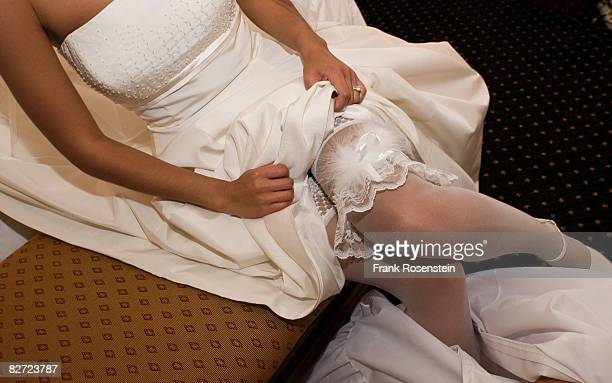 bride displays her garter - garter belts and stockings stock photos and pictures