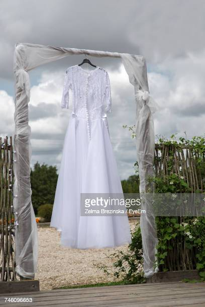 Bride Dress Hanging On Wood Against Cloudy Sky