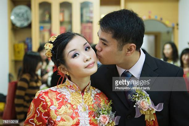 Bride dressed in traditional Chinese clothing, looking at camera as groom kisses her on the cheek