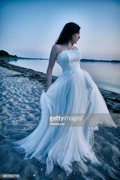 Bride elegantly posing by the sea in the blue hour