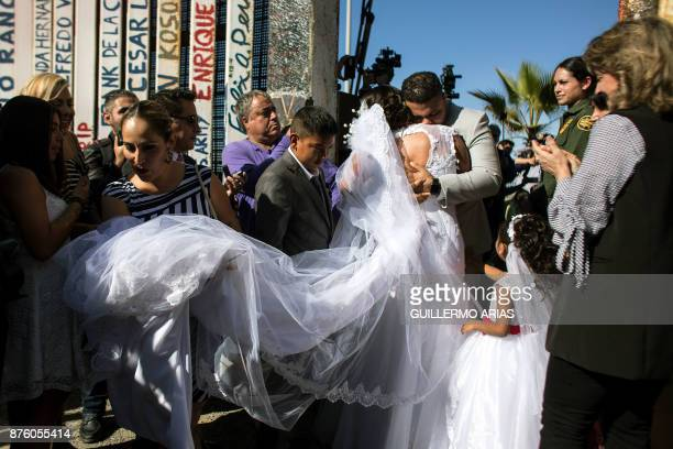 Bride Evelia Reyes and groom Brian Houston living on different sides of the USMexico border stand for a family portrait after getting married during...